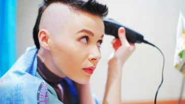 A woman shaving her head in front of the mirror.