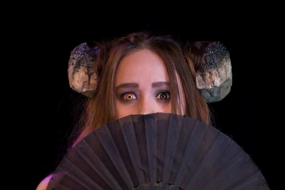 Woman in horned witch costume wearing prosthetic contacts.