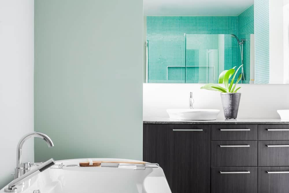 Modern bathroom with white and sage green walls.