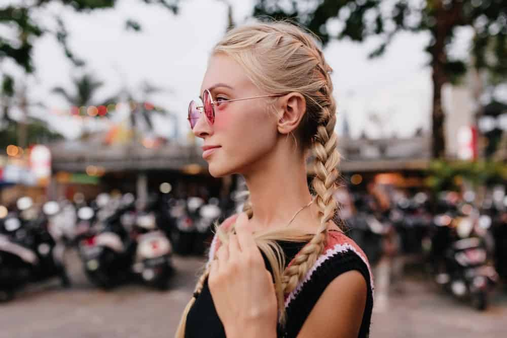 Woman with blonde braided hair in pink sunglasses.