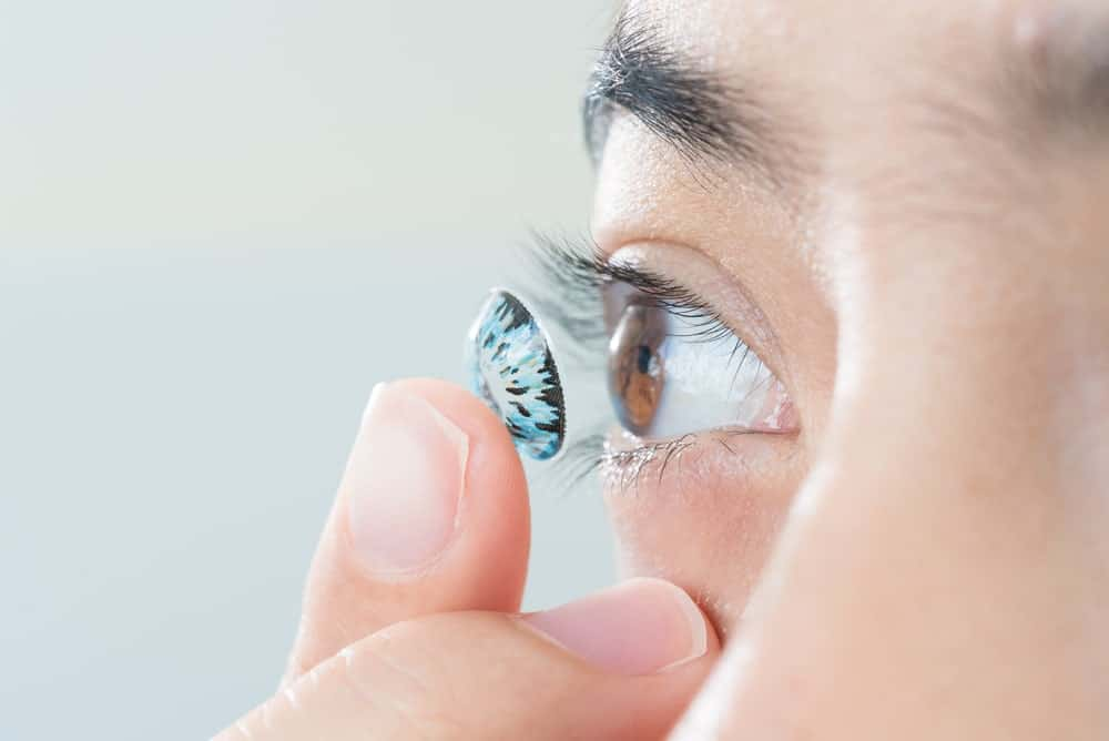 Woman putting colored contact lens in her right eye.
