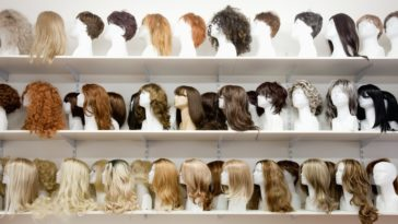 Rows of various wigs on shelves on display at a store.