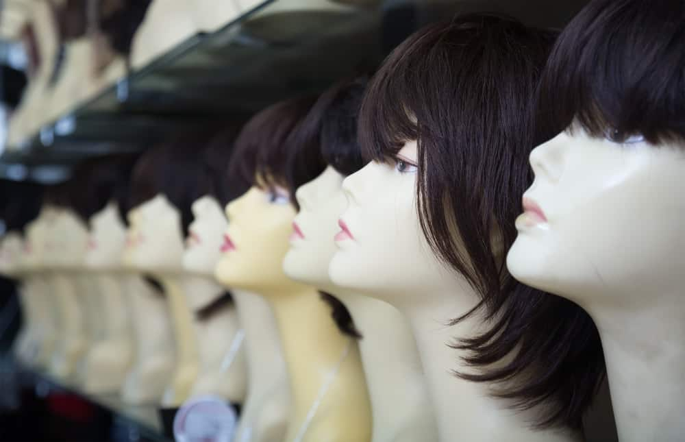 This is a close look at a row of various wigs on display at a store.