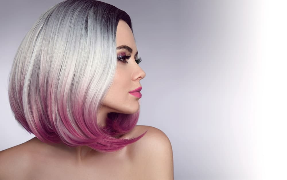 A woman sporting an ombre bob hairstyle with purple highlights.