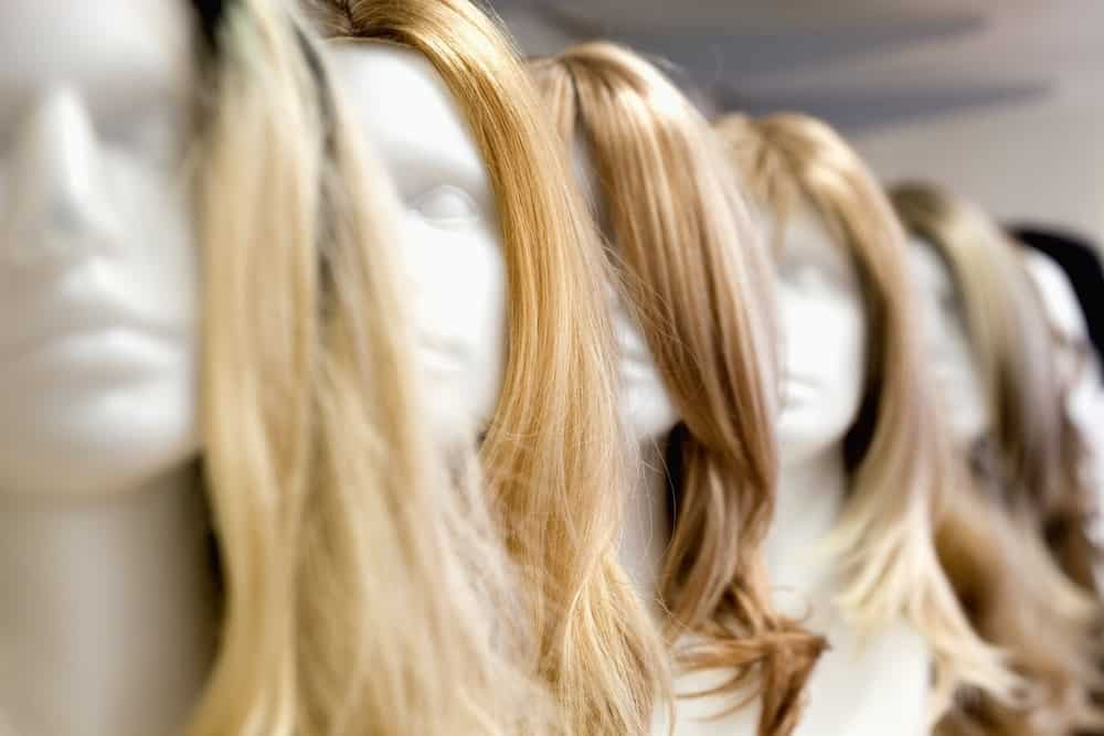 A close look at a row of various wigs on display at a store.