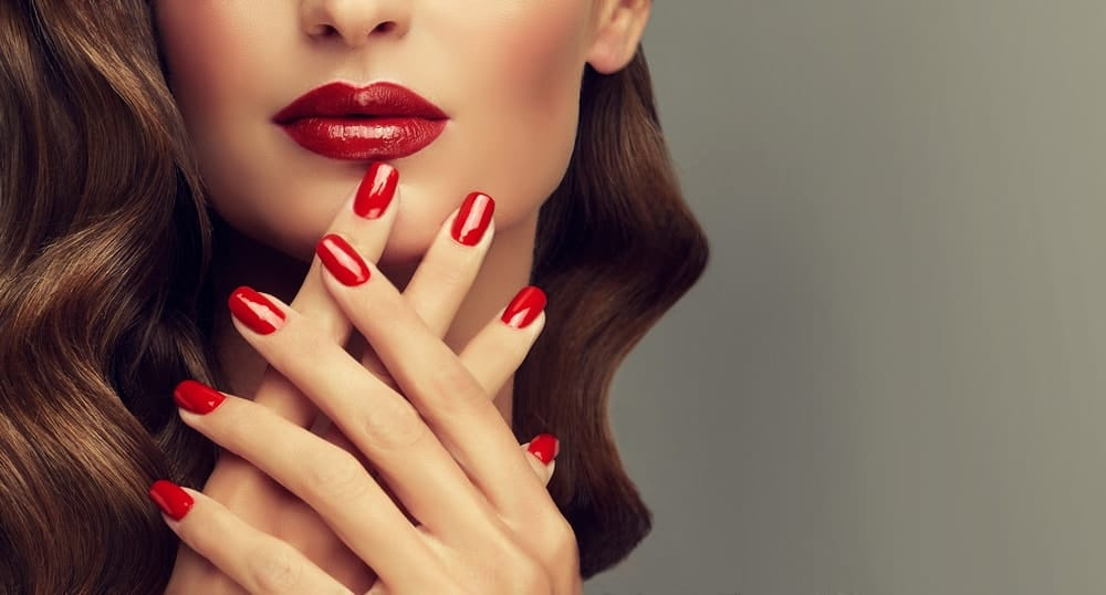 A woman showing off her red fingernails that matches her red lips.