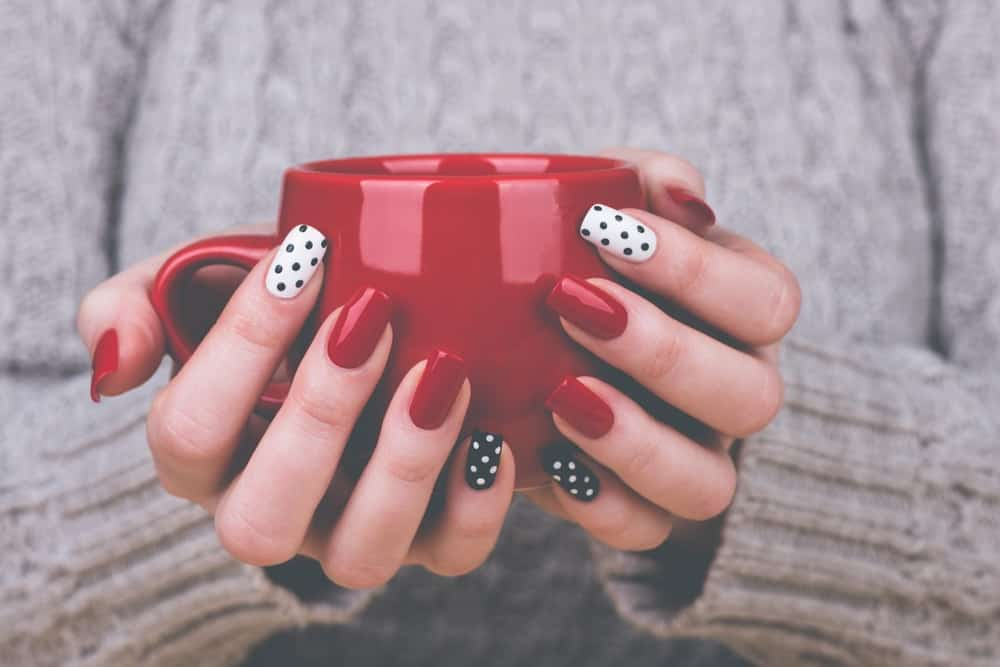 A close look at a woman's hands with various nail polish that is holding a red mug.