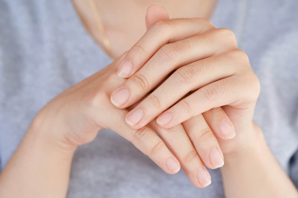 A close look at a woman's hands with a set of healthy nails.