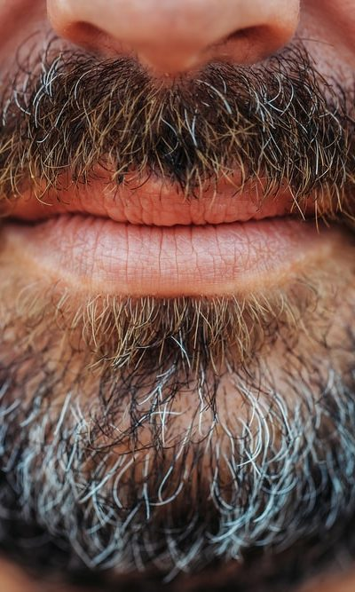 A close look at a full-bearded man with graying hair.