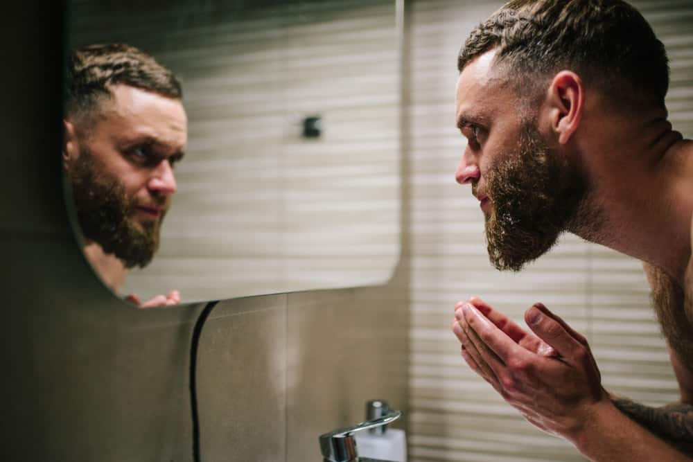 A bearded man washing his face at the bathroom sink.